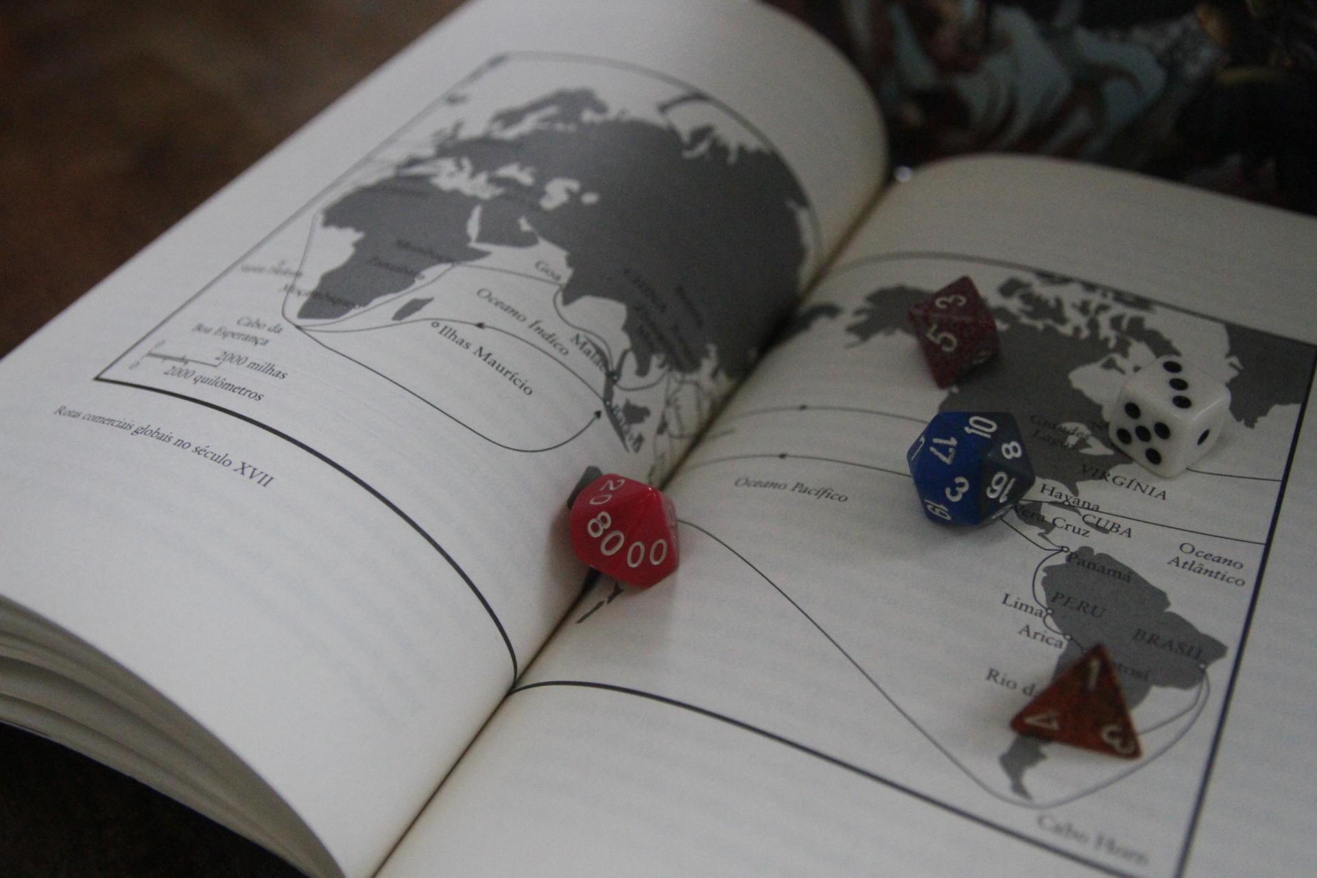 Foto colorida horizontal mostra páginas do livro abertas, com um desenho de mapa em preto e branco ocupando as duas páginas, e sobre o livro cinco diferentes dados