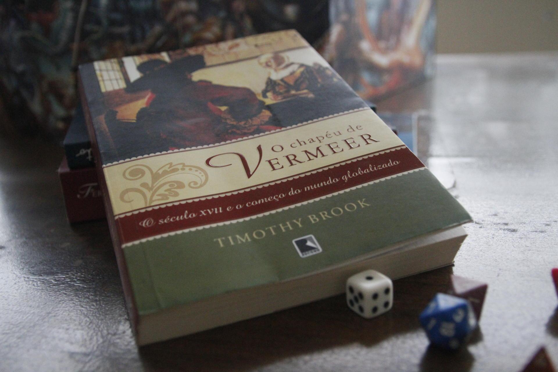 Foto colorida horizontal mostra a capa do livro e dados que serão utilizados no RPG