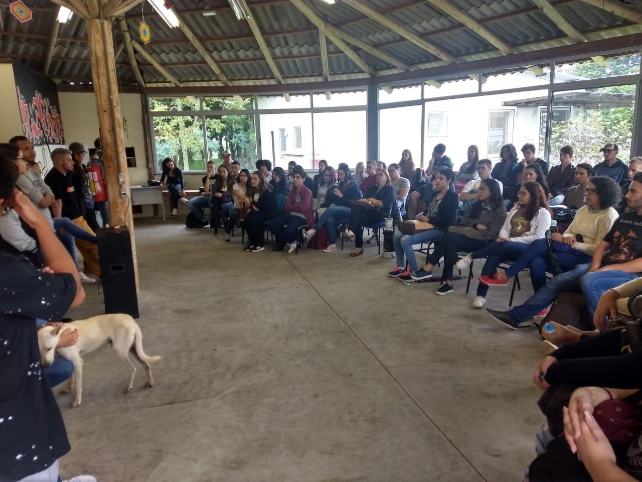 Foto colorida horizontal mostra alunos sentados e em pé, em semicírculo, e à frente alguns alunos em pé falando. A foto também mostra um cachorro sendo acariciado
