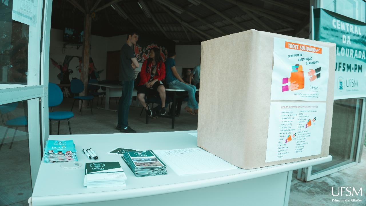 Foto colorida horizontal mostra, em primeiro plano, caixa de coleta da campanha solidária sobre uma mesa, ao lado de folders, e ao fundo alguns jovens conversam