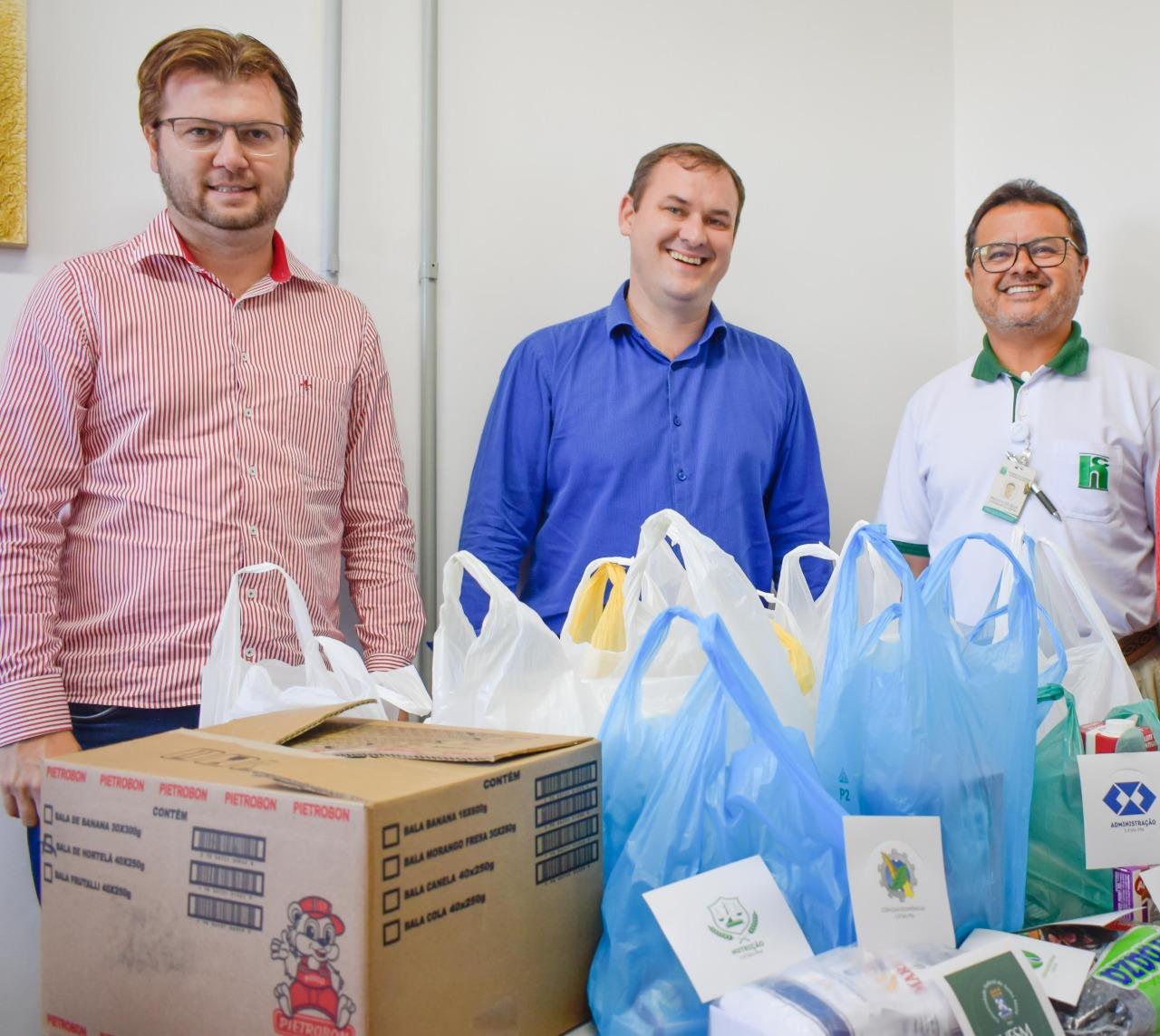 Foto colorida com o diretor do campus ao lado de outros dois homens, representantes do hospital, tendo à frente caixas e sacolas contendo as doações