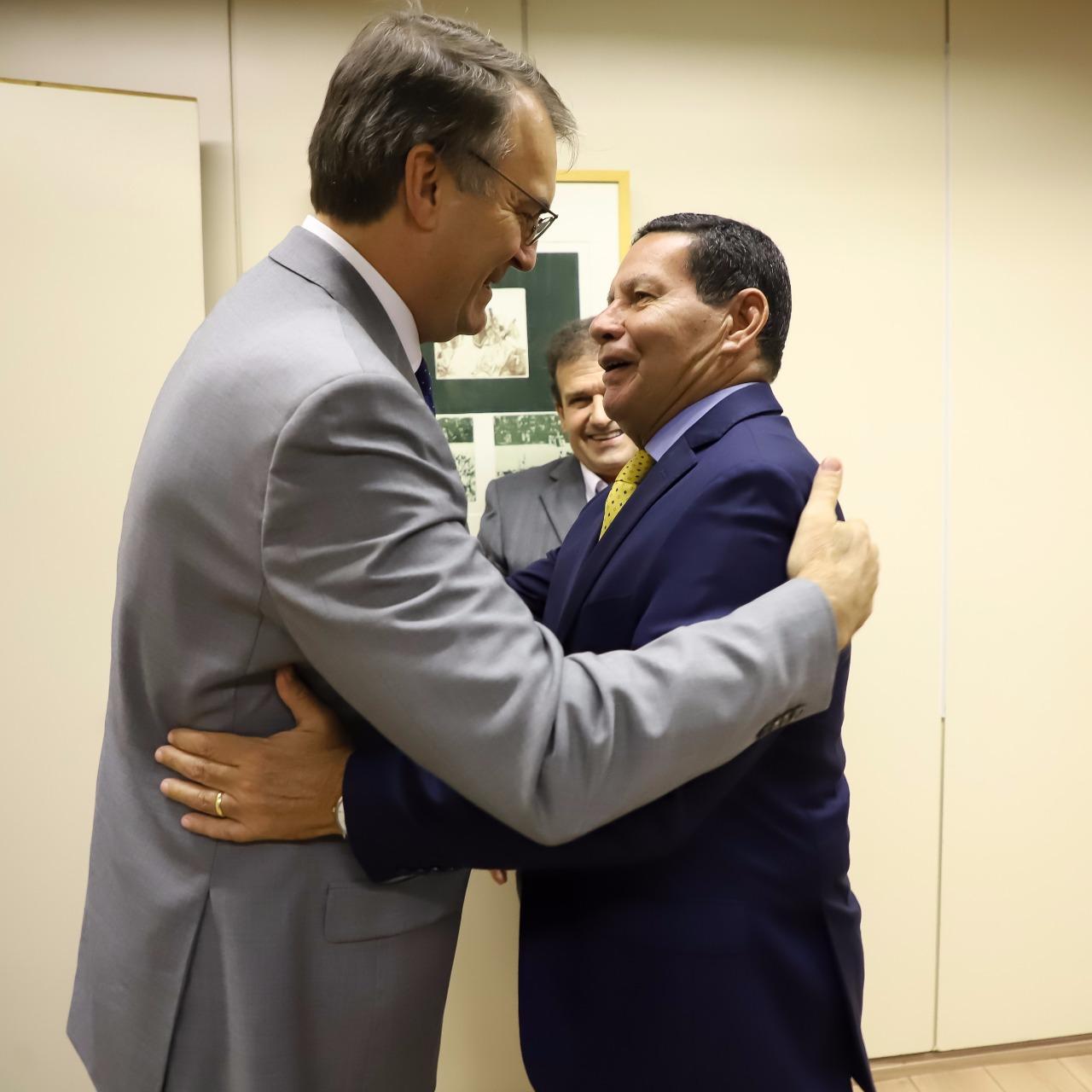 Foto colorida em que Burmann e Mourão aparecem de lado, se abraçando e conversando. Atrás, um homem observa
