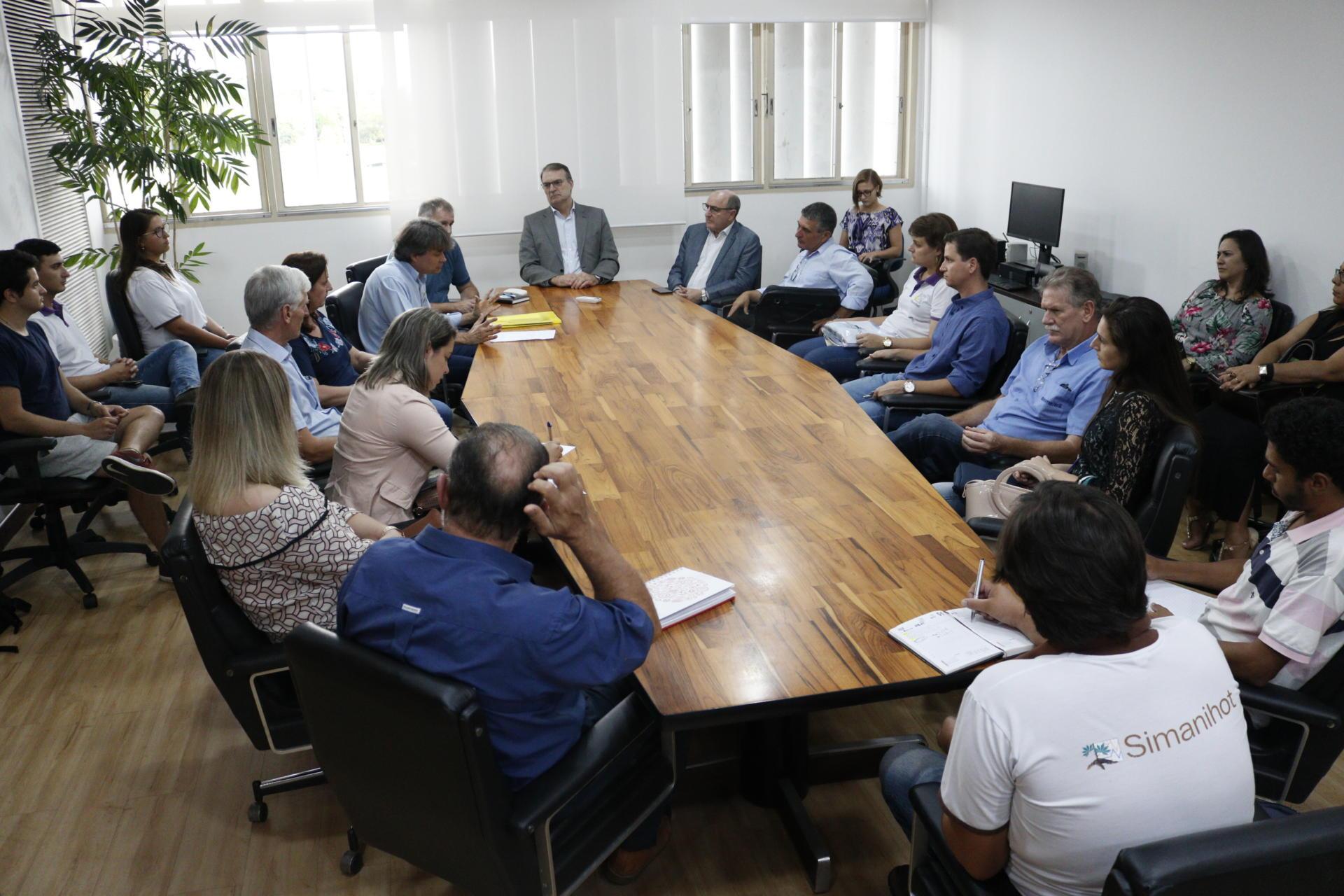 Foto colorida horizontal mostra o reitor sentado na cabeceira da mesa, e outras pessoas ao redor