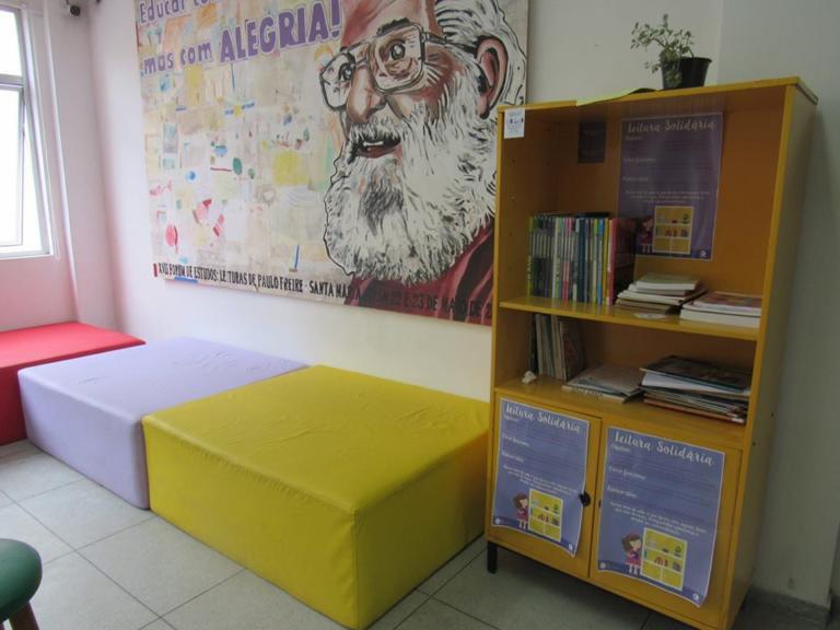 Foto colorida horizontal mostra paletes estofados, nas cores amarelo, branco e vermelho, junto a um armário com livros, e na parede um quadro com uma pintura de Paulo Freire e dizeres