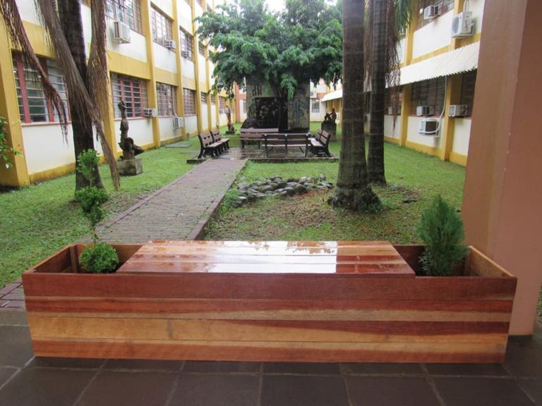 Foto colorida horizontal mostra um banco de madeira, com plantas do lado, e ao fundo uma área verde entre os prédios do CE