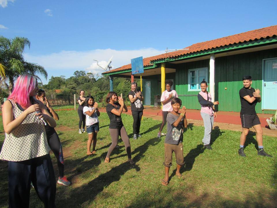 Foto colorida horizontal mostra um grupo de pessoas fazendo movimentos de dança, entre eles crianças indígenas, em um gramado. Ao fundo, casas verdes