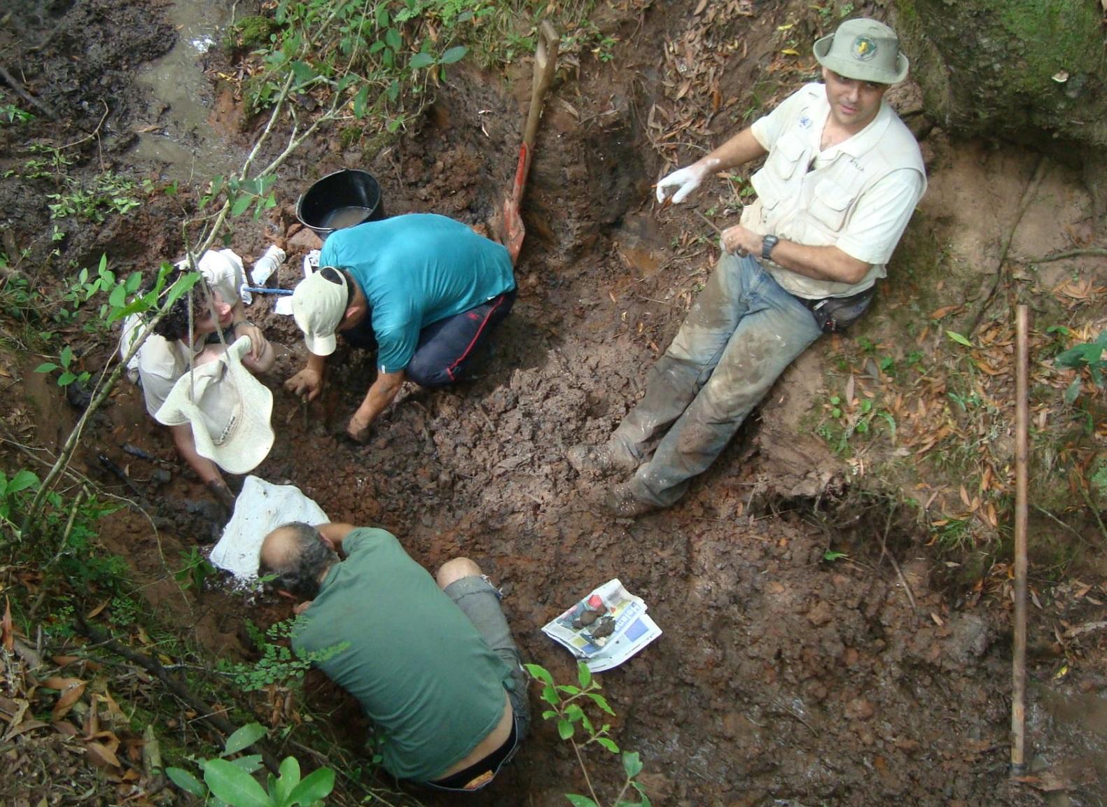 Imagem de escavação, com pesquisadores agachados, retirando fóssil, e outro em pé apontando local da descoberta