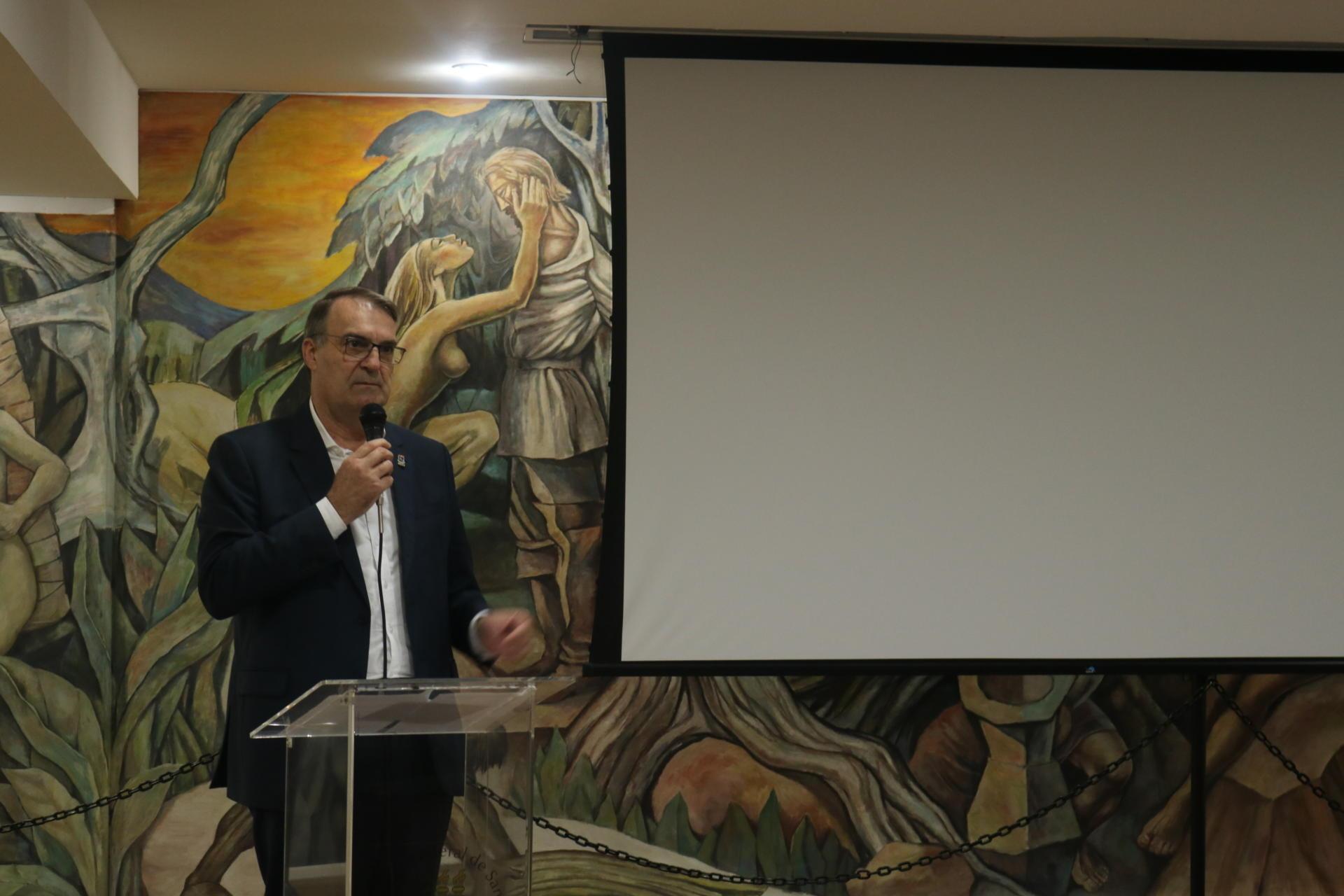 Foto horizontal colorida com o reitor falando ao microfone, tendo ao fundo o painel do salão Imembuí e uma tela para projeções