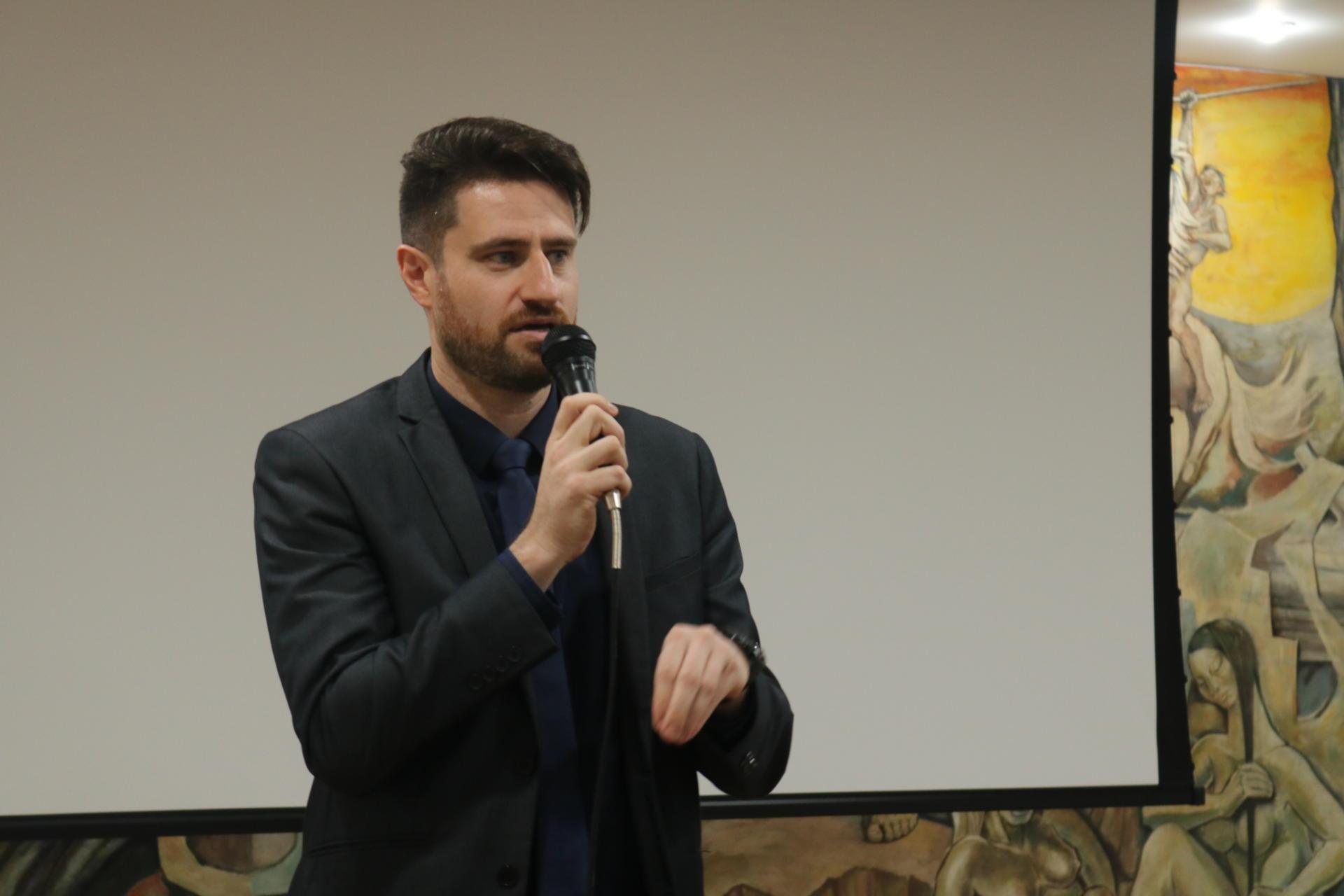 Foto colorida horizontal com Tiago Marchesan falando ao microfone