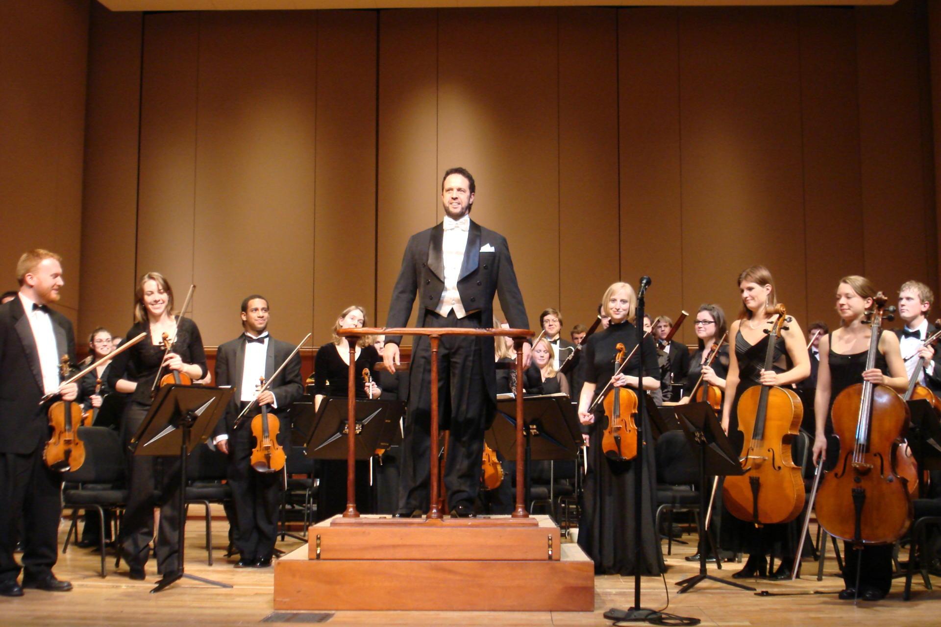 Foto colorida horizontal mostra parte dos integrantes da orquestra em um palco, em pé, com instrumentos na mão, e o maestro ao centro, todos olhando para o público