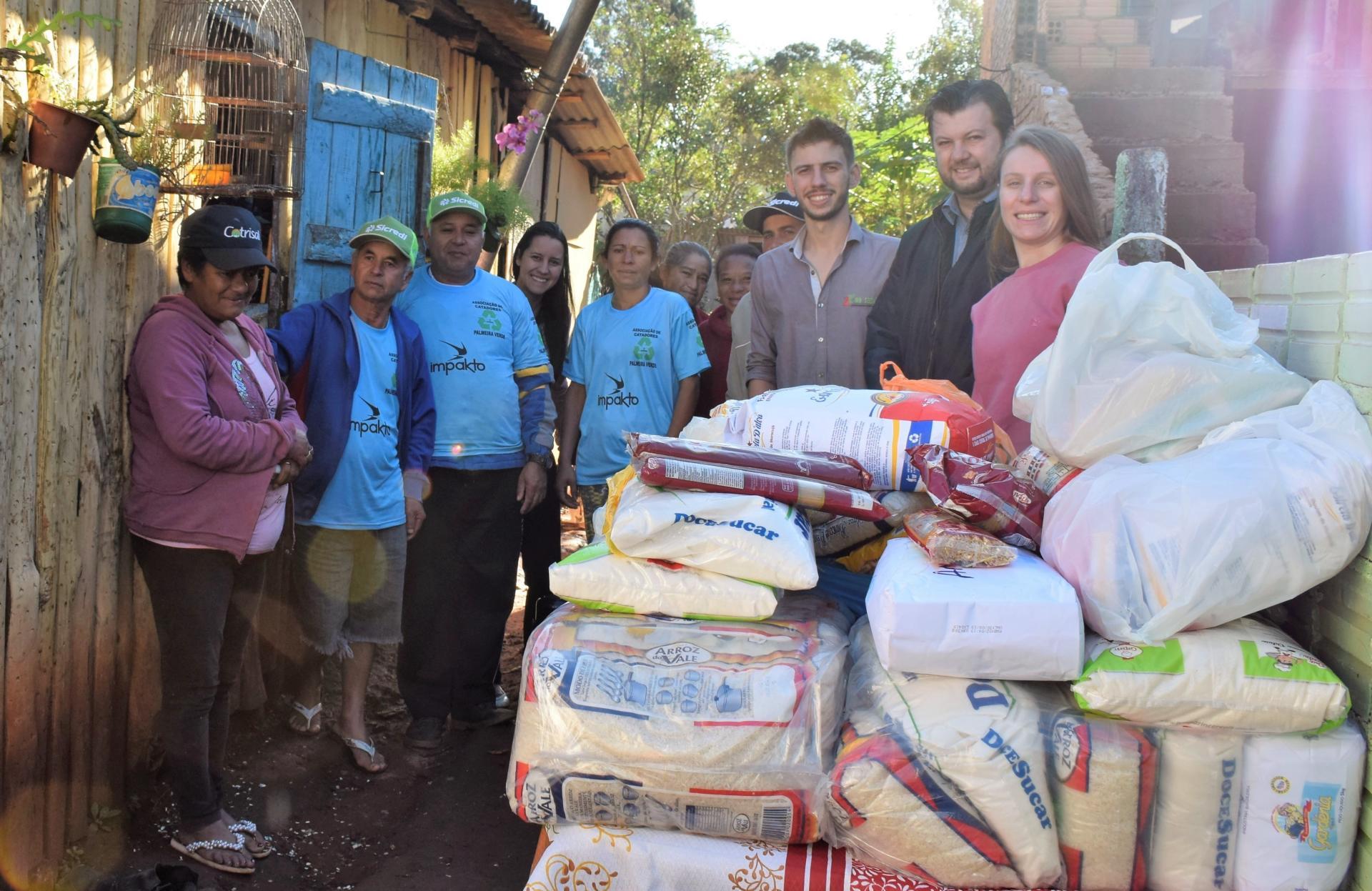 Foto colorida horizontal de pessoas posando atrás de uma pilha de alimentos doados junto a casas de catadores
