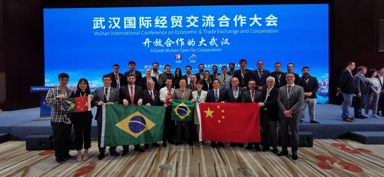 Na foto, grupo de pessoas em pé seguram bandeiras do Brasil e da China