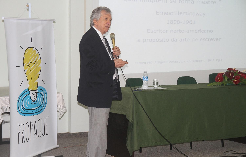 A foto mostra, o palestrante em pé, segurando microfone. À esquerda um cartaz com a marca Propague, que é um lâmpada, e à direita a mesa.