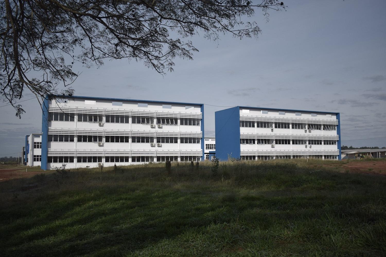 Imagem mostra quatro prédios, dois à frente. Todos têm três andares paredes laterais azuis e paredes frontais em branco