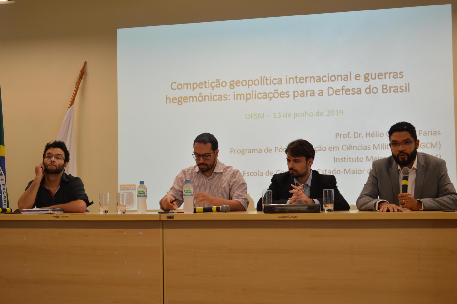 Foto colorida horizontal mostra quatro homens sentados em uma mesa no palco do auditório, voltados ao público, e no fundo um telão com o título da palestra