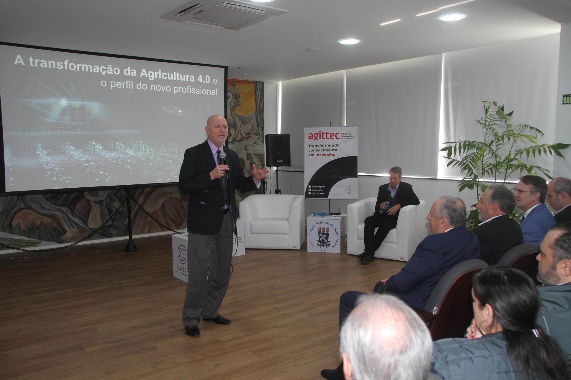 Foto colorida horizontal mostra o palestrante, de terno e gravata, em pé, falando ao público, no Salão Imembuí, com um telão com o título da palestra ao fundo