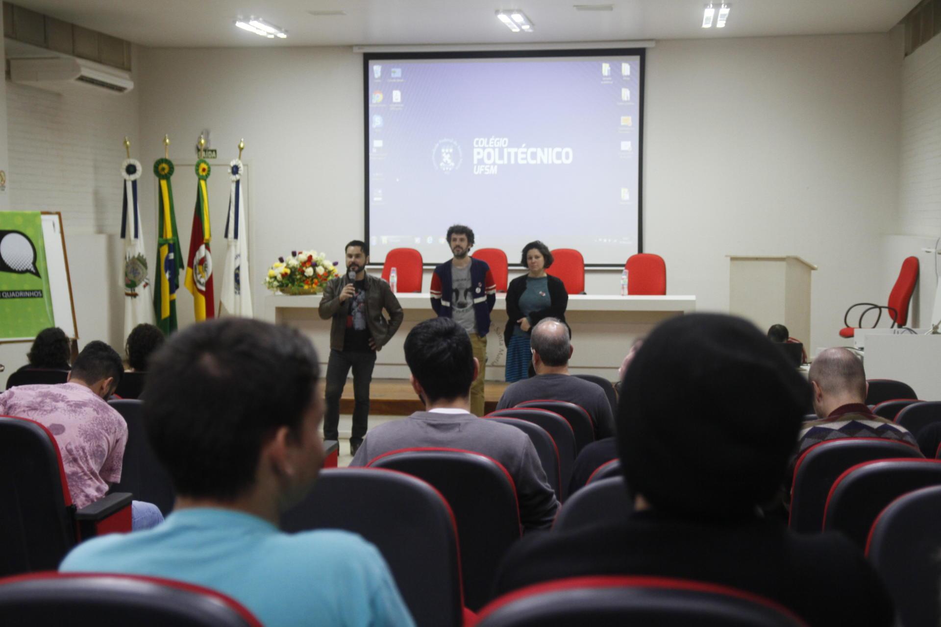 Foto colorida horizontal mostra três pessoas falando ao público em um auditório