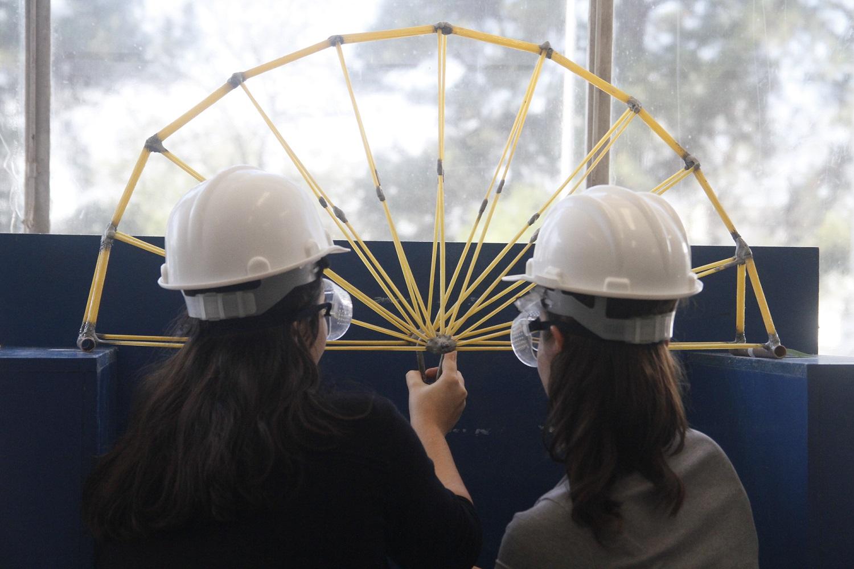 Na imagem, duas alunas de costas seguram ponte de espaguetes que formam um arco