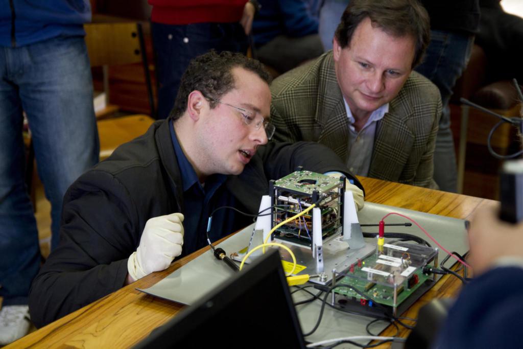 Na foto, um homem ajusta um dispositivo eletrônico retangular em uma plataforma metálica. Um segundo homem observa. Os dois estão agachados.