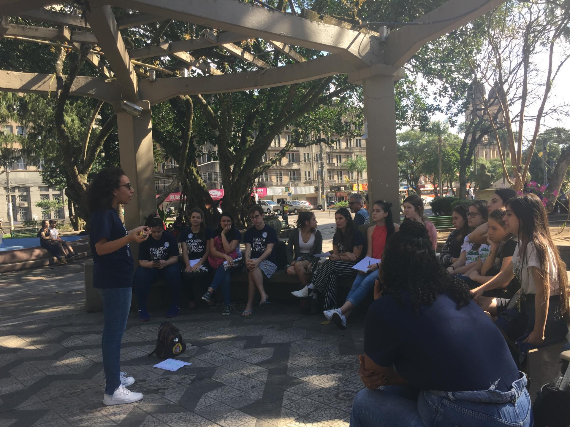 Foto colorida horizontal mostra uma pessoa em pé e outras sentadas ouvindo-a no coreto da praça