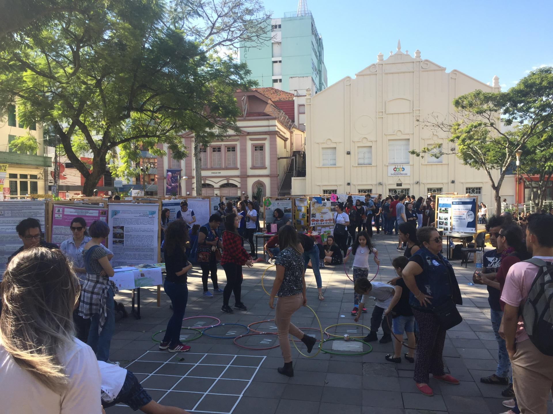 Foto colorida horizontal mostra pessoas conversando, olhando os banners e crianças brincando com bambolês dispostos no chão da praça