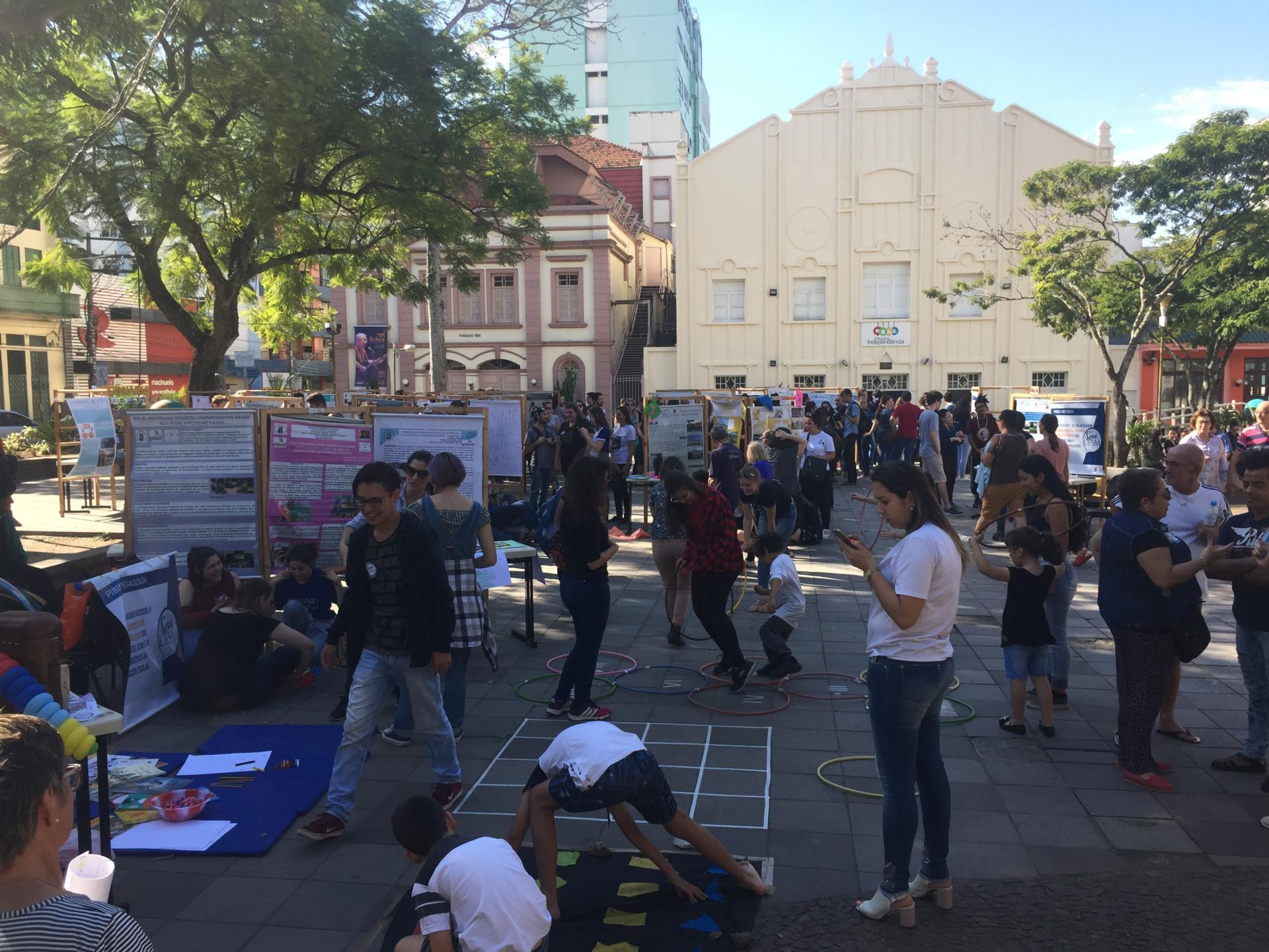 Foto colorida horizontal mostra pessoas em pé, sentadas no chão, crianças brincando no chão, banners armados na praça, tendo ao fundo o Teatro Treze de Maio e o Shopping Independência
