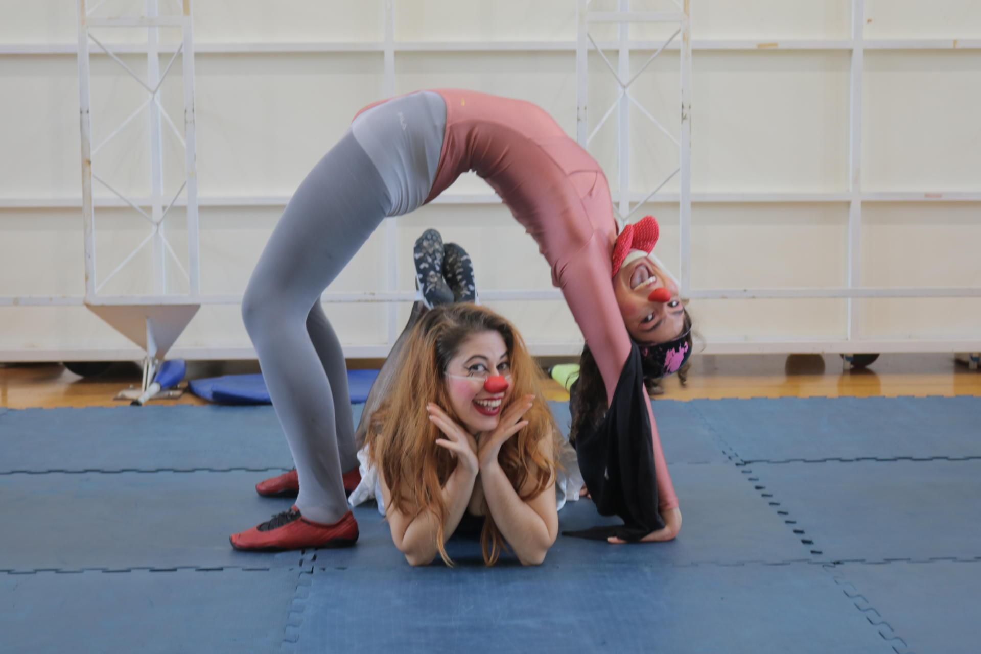 Foto colorida horizontal com duas mulheres com o rosto pintado de palhaço fazendo acrobacias. Uma deitada, as mãos seguram o queixo, e a outra faz um semicírculo sobre ela