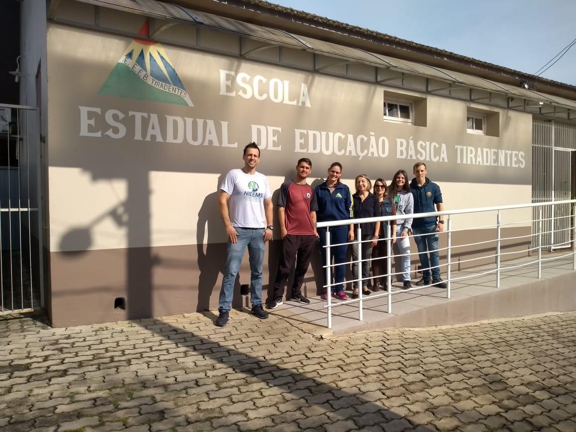 Foto colorida horizontal mostra sete pessoas, homens e mulheres, posando para a foto em frente à escola, cujo nome e logo aparecem pintados na parede
