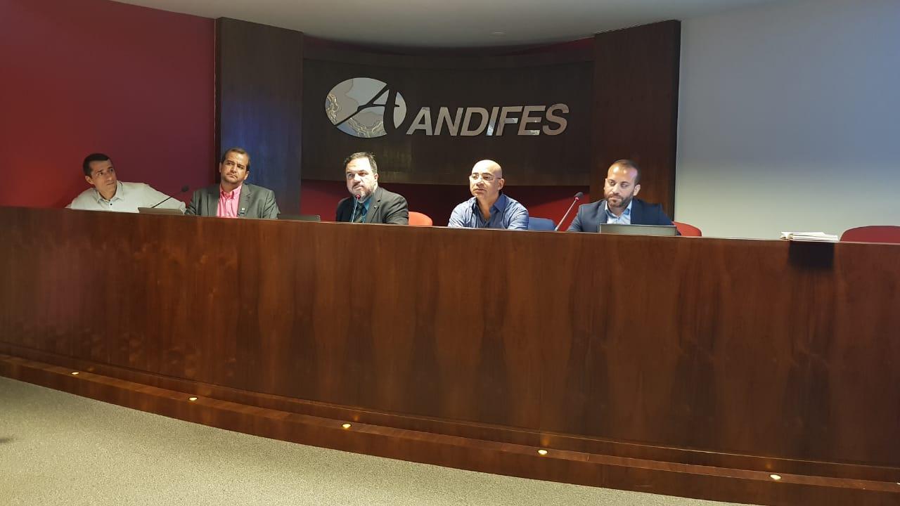 Foto colorida horizontal mostra cinco homens sentados em uma bancada, com a palavra Andifes ao fundo