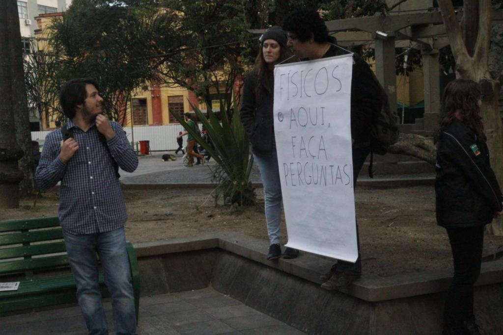 Homem usa cartaz preso ao pescoço com o seguinte texto 'Físicos aqui, faça perguntas'