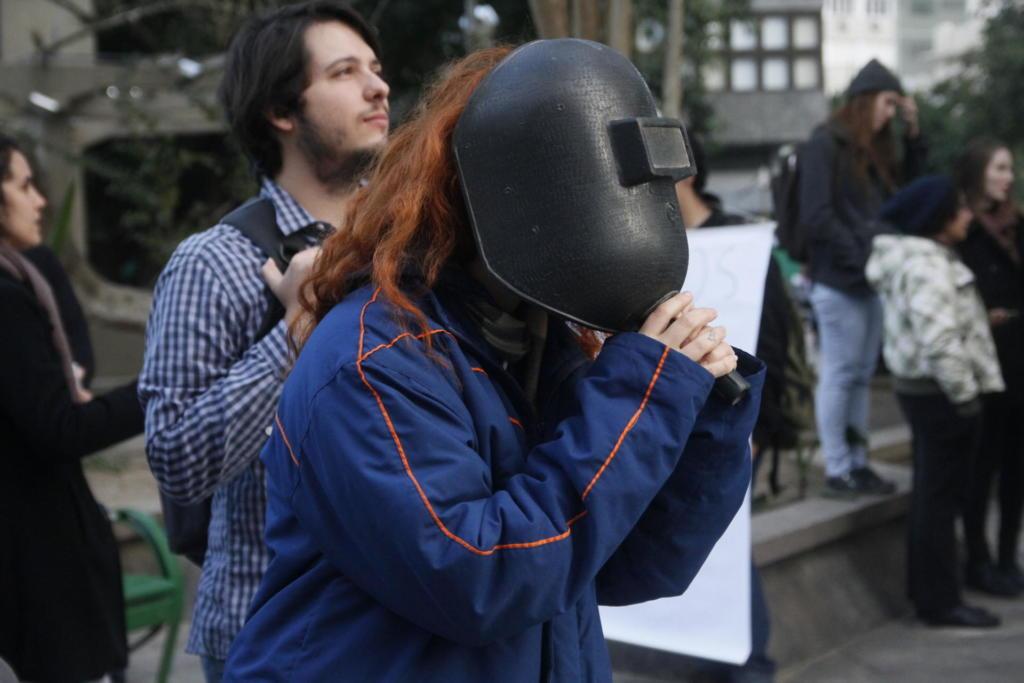 Na foto, em primeiro plano, uma mulher jovem usa uma máscara de soldador. Atrás dela um um homem jovem olha para o céu a olho nu