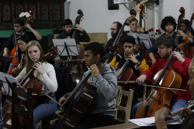 Foto mostra grupo de músicos, sentados, tocando violoncelo enquanto olham para partituras