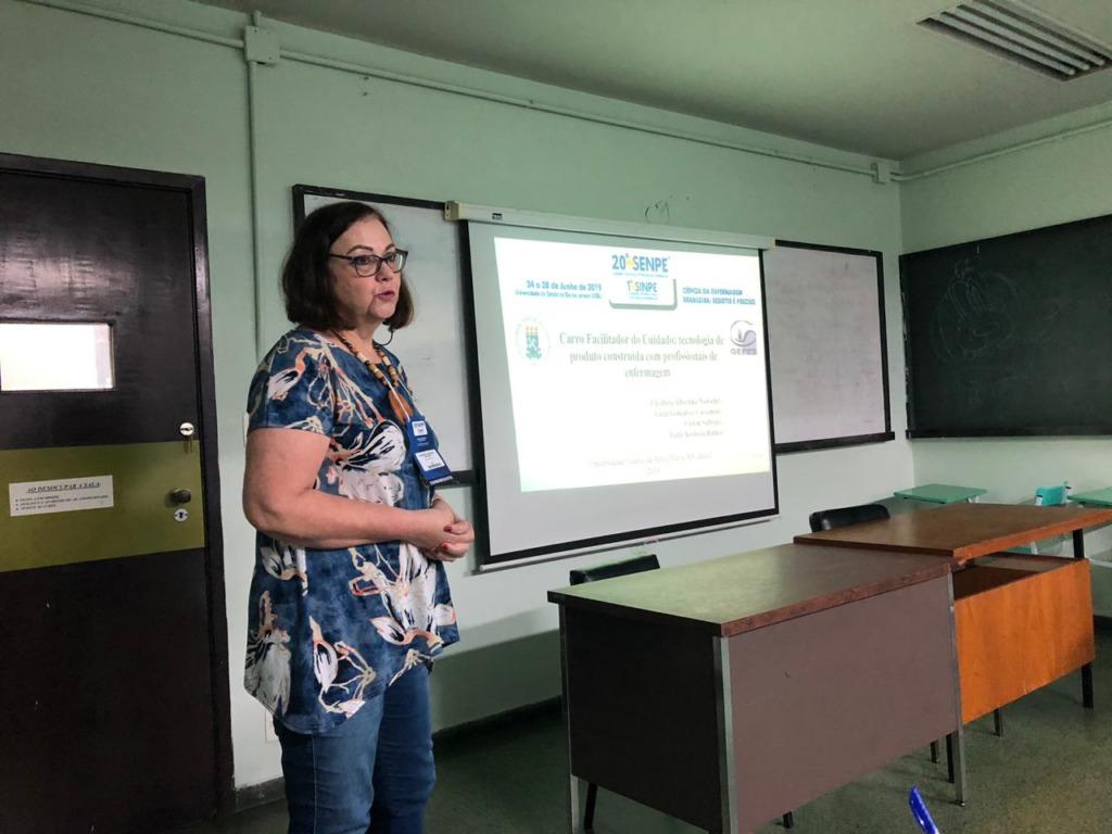 Foto colorida horizontal mostra uma mulher de cabelo escuro na altura do pescoço, de óculos, blusa de estampas com fundo azul, falando a um público que não aparece, em uma sala de aula