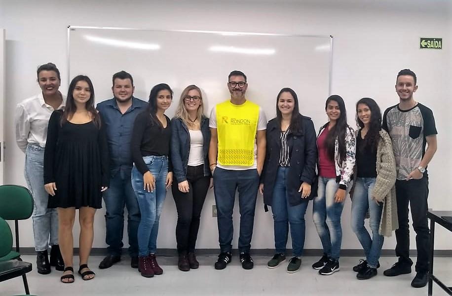 Foto colorida horizontal com 10 pessoas, homens e mulheres, lado a lado, posando para a foto. Eles sorriem tendo ao fundo uma parede branca com uma lousa