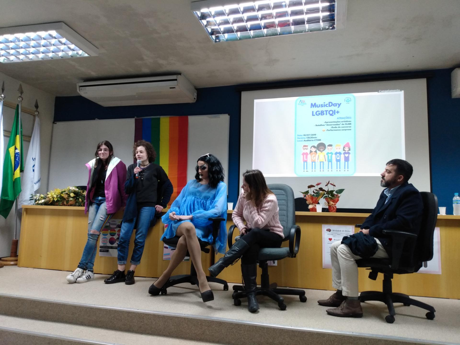 Foto colorida horizontal mostra cinco pessoas no palco do auditório, três sentadas e duas em pé, falando ao público