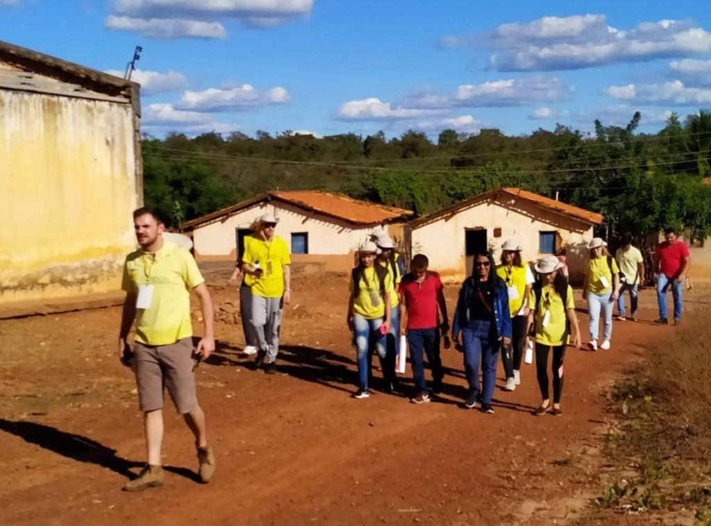 Na foto, grupo de pessoas caminha em caminho de chão batido em dia ensolarado. Pode-se notar pequenas casas de alvenaria.