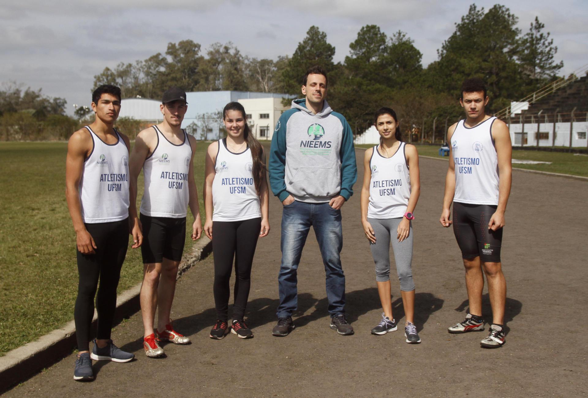 Foto colorida horizontal mostra cinco alunos de uniforme (regata branca) e o professor na pista de atletismo posando de frente para a foto