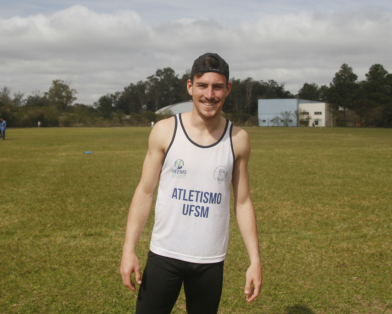 Foto colorida mostra o atleta posando para foto na pista de atletismo do Cefd