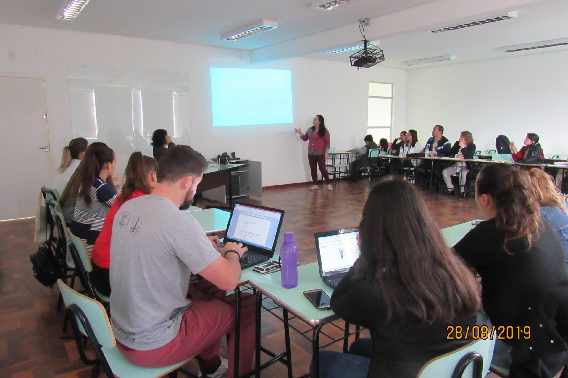 Foto colorida horizontal mostra pessoas em uma sala de aula, sentadas em semicírculo, e à frente uma mulher explana com um retroprojetor