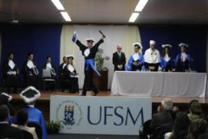 Foto colorida horizontal mostra um formando erguendo as duas mãos no palco, após ter recebido o diploma