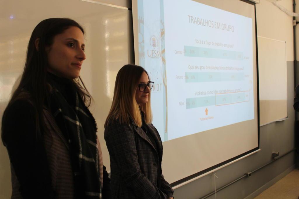 Duas mulheres em pé à frente de uma apresentação em slides