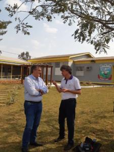 A imagem mostra o reitor e o professor Nereu. Ambos estão em pé em frente à escola