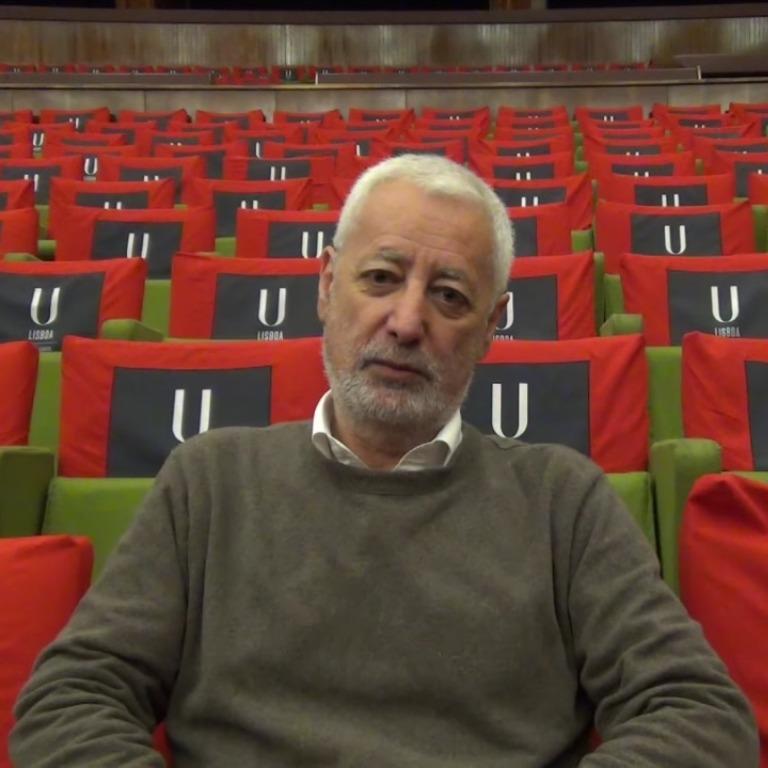 Foto do professor sentado em um auditório
