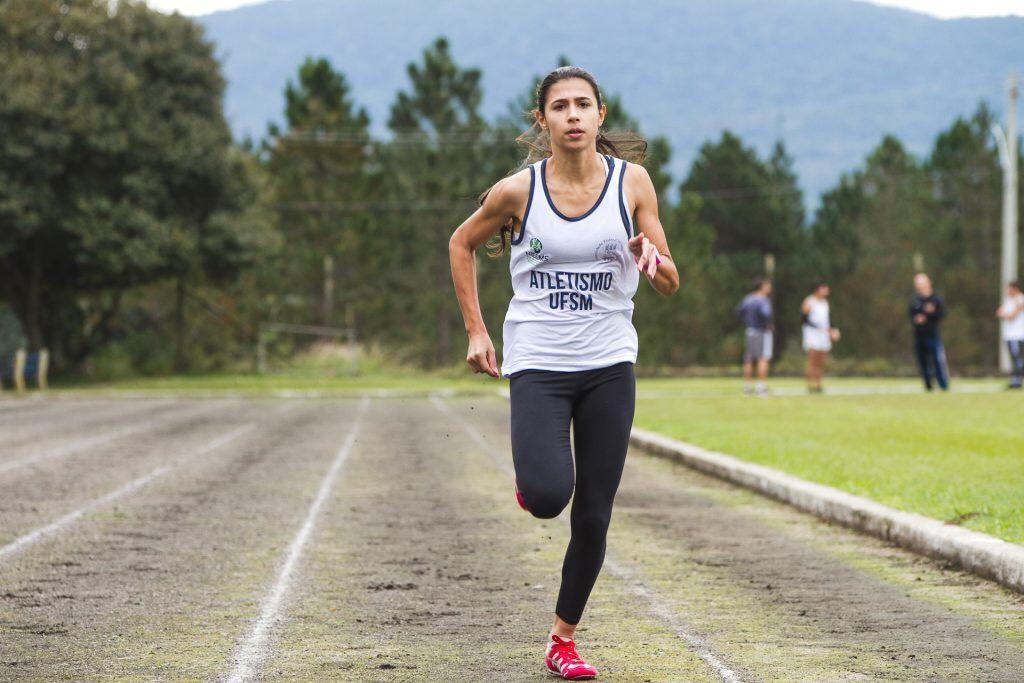 Em primeiro plano, atleta corre em pista de corrida.