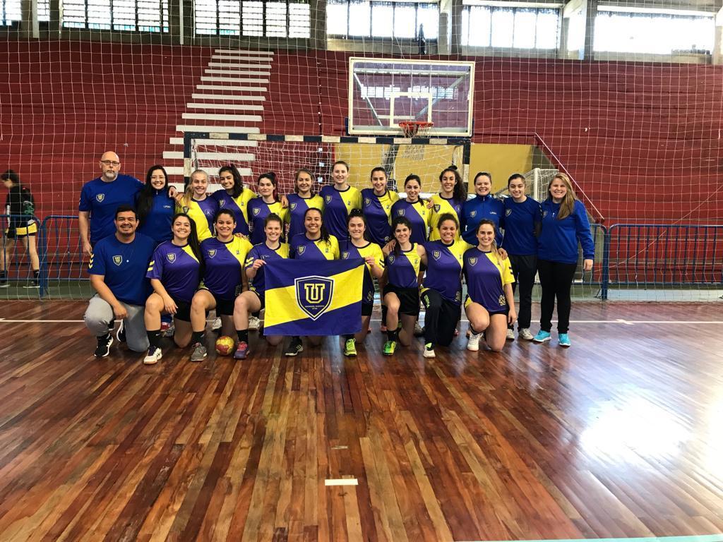 Foto colorida horizontal mostra a equipe com uniforme azul e amarelo em uma quadra de esportes, alguns agachados e outros em pé
