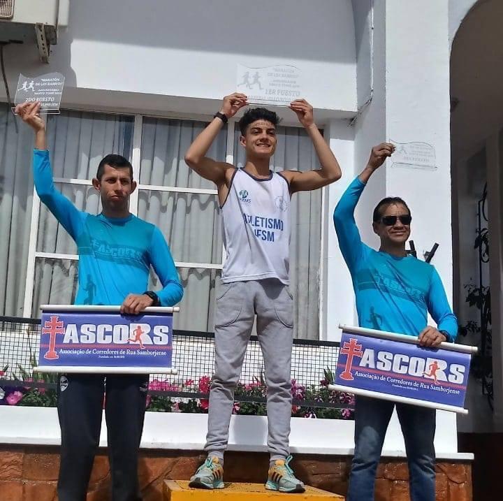 Foto colorida em formato quadrado mostra os 3 atletas que subiram ao pódio, com as mãos para cima segurando troféus, o atleta vencedor usa uma regata do atletismo UFSM