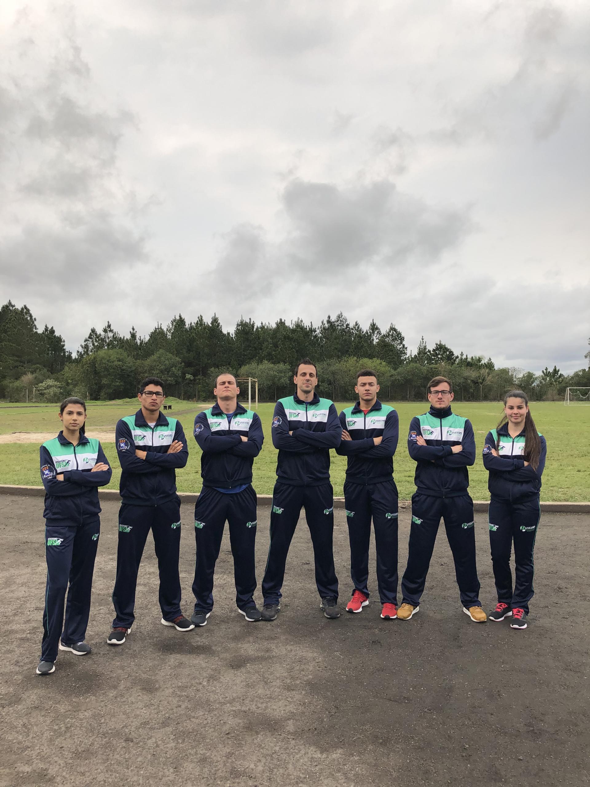 Foto vertical colorida mostra sete homens e mulheres posando para foto na pista de atletismo do Cefd em um dia nublado. Eles estão de braços cruzados e usando uniforme marinho com detalhes em branco e verde claro