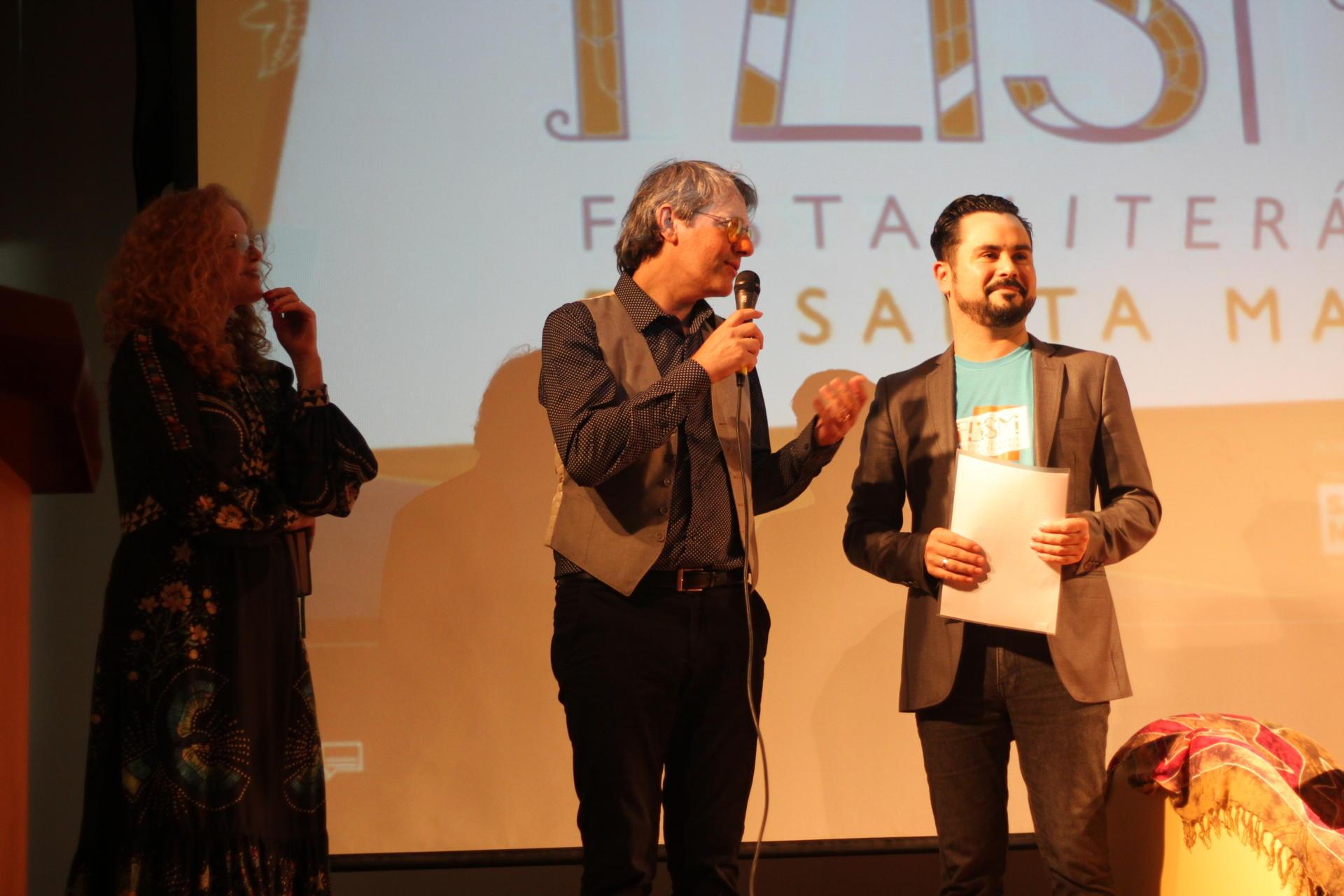 Foto colorida horizontal mostra em primeiro plano os três professores no palco do evento, com iluminação reduzida em tons amarelos, um deles fala ao microfone