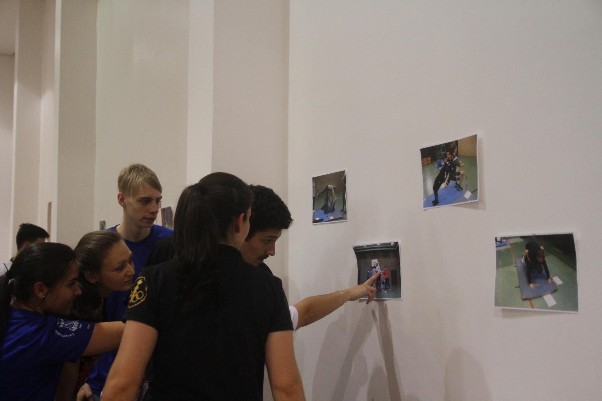 Estudantes avaliam fotos fixadas na parede, que representam diferentes movimentos