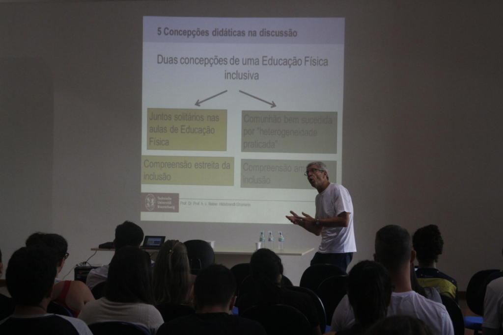 À frente professor apresenta palestra enquanto público observa